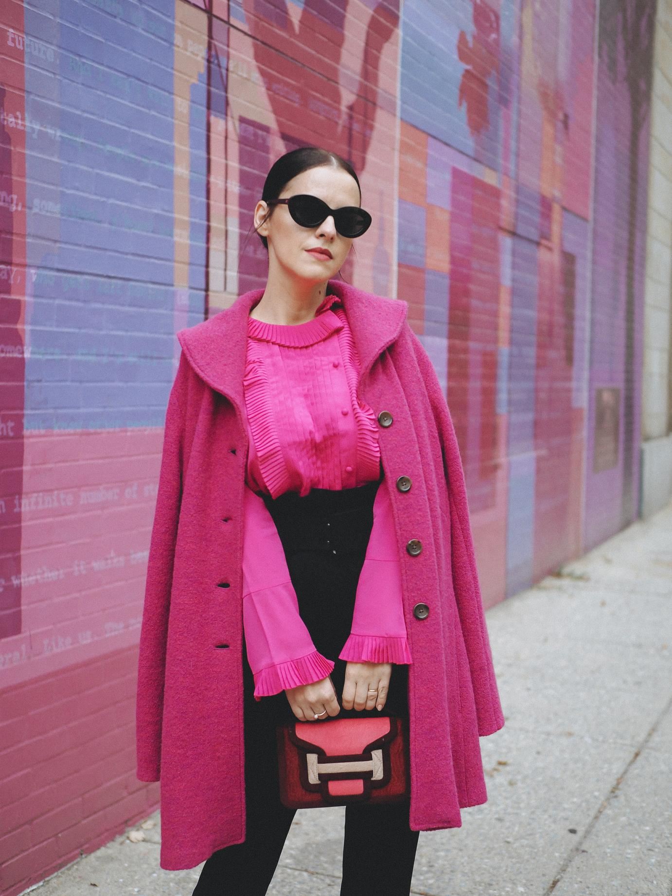 "Another popping mix of color is in full display today. This time Fuchsia is the main color and I have not one, but 3 pieces (if I count the hints from the bag, I have 4) in this color. The coat is a vintage piece, old in my closet. I am happy to wear it again in a mix with this black pair of belted high trousers and this ruffled shirt. It's quite a ""loud"" color combination so there's no need for more accessories if you ask me!"